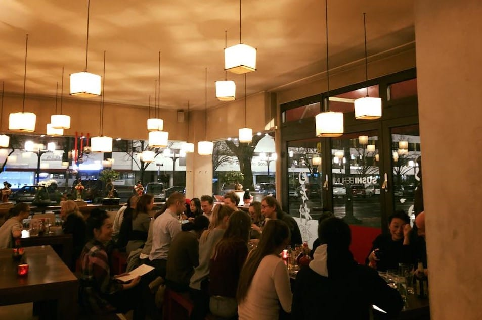 People eating at Sushi Berlin, cubic decoration lamps and glass walls to the street