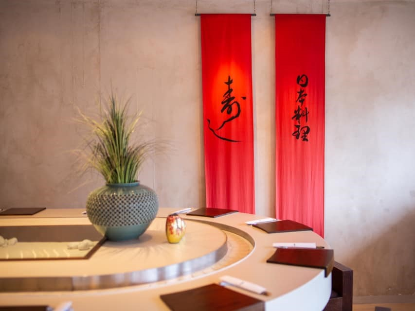 Two long red flags with japanese writings and part of the sushi bar with tables and plants